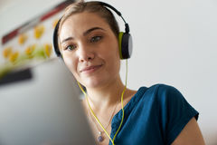 Woman With Green Earphones Listens Podcast Music On Tablet. Beautiful woman relaxes on sofa and watches podcast on tablet pc, listening with green big earphones Stock Image