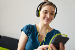 Woman With Green Earphones Listens Podcast Music On Telephone Stock Photos