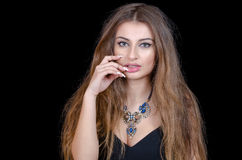 Woman with green eye contact lens , long hair and big necklace. Woman with green eye contact lens, long hair , big necklace and black decollete shirt.  Fingers Royalty Free Stock Images