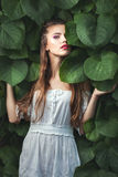 Woman with green eyes among nature. Young woman with green eyes among green leaves of trees in nature Stock Photos