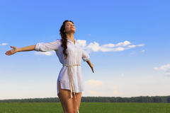 Woman in green field. Young happy caucasian brunette woman in green field, evening light Stock Images