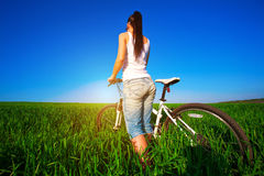 Woman in a green field on a bike. back Stock Photography