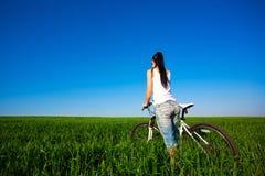 Woman in a green field on a bike Stock Photo