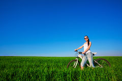 Woman in a green field on a bike Royalty Free Stock Images