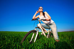 Woman in a green field on a bike Royalty Free Stock Photography