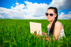 Woman in a green field with a laptop. summer Stock Image