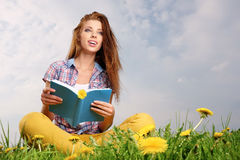 Woman on green field and reads book. Stock Photography