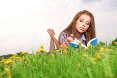 Woman on green field and reads book. Royalty Free Stock Photo