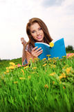 Woman on green field and reads book. Royalty Free Stock Photography
