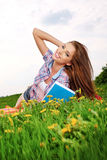 Woman on green field and reads book. Royalty Free Stock Images