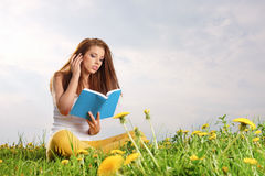 Woman on green field and reads book. Stock Image