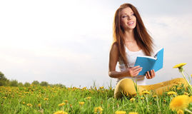 Woman on green field and reads book. Stock Images