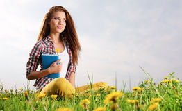 Woman on green field and reads book. Royalty Free Stock Photos