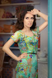 Woman in Green Floral Dress in Fashion Store. Portrait of a trendy girl in a fashion boutique Royalty Free Stock Image