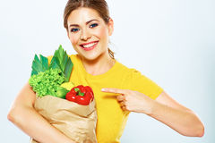 Woman with green food points a finger at the produ Stock Images
