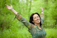 Woman in green forest. Happy woman smiling and raising arms in verdant forest Stock Images