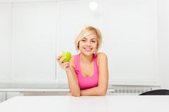 Woman green fresh apple in her kitchen at home Royalty Free Stock Photos