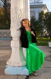 Woman in green and fur coat stand near column Royalty Free Stock Photo