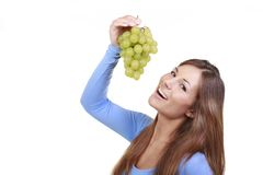 Woman with green grapes. Isolated on white stock photography
