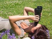 Woman on green grass and binoculars. Young woman looking through a black binoculars Royalty Free Stock Photo