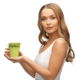 Woman with green grass in pot Stock Images