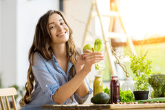Woman with green healthy food and drinks at home. Beautiful happy woman sitting with drinks and healthy green food at home. Vegan meal and detox concept Stock Photos