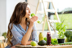 Woman with green healthy food and drinks at home. Beautiful woman sitting with drinks and healthy green food at home. Vegan meal and detox concept Stock Photos