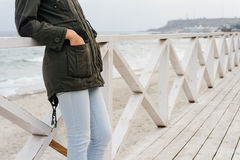 Woman in a green jacket and blue jeans standing on the wooden promenade near the sea Royalty Free Stock Photos