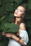 Woman with a green leaf. Portrait of a young woman in nature, in her hands she is holding a green leaf of a tree Stock Images