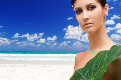 Woman with green leaf on tropical beach Stock Photos