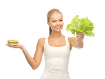 Woman with green leaves and hamburger Stock Photography