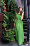 Woman in green long dress walking outside her home Royalty Free Stock Photo