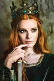Woman in green medieval dress. Portrait of a beautiful red-haired woman in green medieval dress Royalty Free Stock Images
