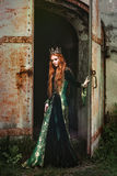 Woman in green medieval dress. Portrait of a beautiful red-haired woman in green medieval dress royalty free stock image