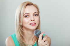 Woman in green with microphone Stock Photography