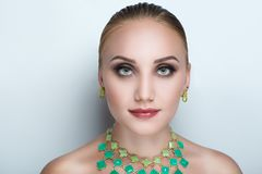 Woman green necklace. Closeup portrait of beautiful girl woman lady with professional make up and hair styling. Luxury accessory New Bright color makeup, shiny Stock Image