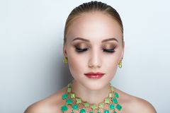 Woman green necklace. Closeup portrait of beautiful girl woman lady with professional make up and hair styling. Luxury accessory New Bright color makeup, shiny Royalty Free Stock Photography