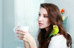 Woman with green parrot Stock Image