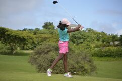 Woman in Green Polo Shirt and Pink Shorts Playing Golf Under Grey and Blue Skies during Daytime Stock Photos