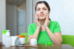 Woman in green puts cream on face Royalty Free Stock Photo
