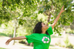 Woman in green recycling t-shirt touching leaves at park Royalty Free Stock Photo