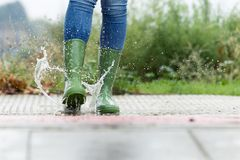 Woman in green rubber boots jumping on the puddle water in the street. stock image