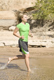 Woman in green running in water. A woman in green running in the lake with out shoes Royalty Free Stock Image