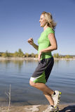 Woman in green runs at lake. A woman running on rocks by the lake Royalty Free Stock Photography