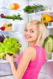 Woman green salad diet, refrigerator Royalty Free Stock Photos