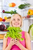 Woman green salad think look up, refrigerator. Young woman hold fresh green salad diet think look up, refrigerator open door, pretty ponder girl dieting dream Stock Photos