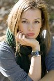 Woman in green scarf. Portrait of young brunette woman in green scarf. She resting her chin on her hand Stock Photo