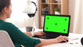 Woman with green screen on laptop at home stock video