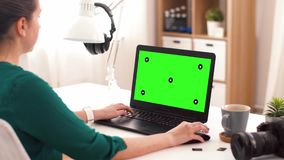 Woman with green screen on laptop at home stock footage