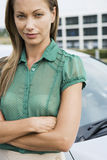 Woman in green short-sleeved blouse standing beside car, arms folded, close-up, portrait Stock Photo